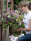 Frau steckt Wiesenblumenstrauß in Korbvase