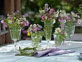 Kleine Wiesenblumen-Sträuße in Gläsern