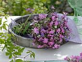 Rosa Wiesenblumen-Strauß auf Holztablett
