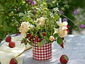 Strauß aus Rosa (Rosen) und Erdbeeren (Fragaria)