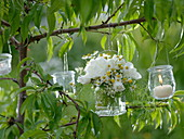 Weißer Kräuterstrauß im Glas und kleine Windlichter an Baum gehängt : 2/2