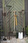 Gartengeräte an der Tür vom Geräteschuppen