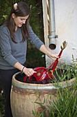 Frau schöpft Wasser aus Wasserfass