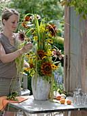 Frau steckt hohen Strauß mit Helianthus (Sonnenblumen), Solidago