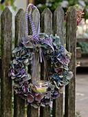 Kranz aus Hydrangea (Hortensienblüten) mit Windlicht am Zaun angebunden