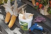 Erntedank-Gesteck in Joghurteimer mit Maisblättern beklebt 1/3