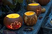 Leuchtende Kürbisse mit Blätterdeko geschnitzt