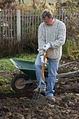 Mann gräbt Erde mit Grabgabel um, Schubkarre