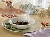 Räuchern mit selbstgetrockneten Kräutern wie Salbei (Salvia) und Rosa