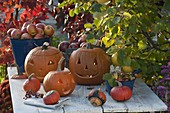 Fröhliche Kürbisköpfe auf Holztisch