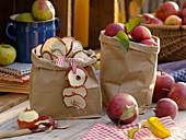 Papiertüten mit Äpfeln und getrockneten Apfelscheiben (Malus)