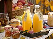 Flaschen mit frisch gepresstem Apfelsaft, Gläser mit Gelee und Apfelmus