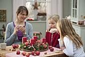 Mutter mit Töchtern bastelt Adventskranz