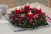 Adventskranz aus Ilex (Stechpalme) mit roten Kerzen, Äpfeln und Zieräpfeln