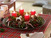 Natürlich dekorierter Adventskranz aus Ilex (Stechpalme) mit roten Kerzen
