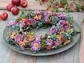 Herbstlicher Kranz aus Clematisranken dekoriert mit Chrysanthemum