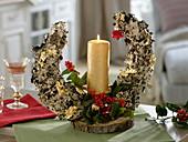 Mit Flechten beklebter Halbmond als Kerzendeko mit Ilex (Stechpalme)