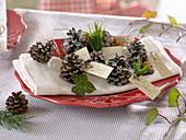 Selbstgemachte Platzkarten aus Zapfen von Pinus (Kiefer) mit Hedera
