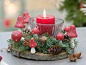 Windlicht mit roter Kerze auf Baumscheibe, dekoriert mit Abies nobilis