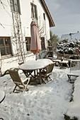 Verschneite Terrasse am Haus mit Sitzgruppe aus Holz