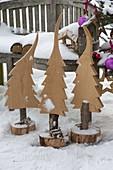 Holz-Tannenbäume in Baumscheiben vor Bank, Vogelfutterhaus