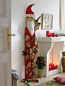 Holz-Nikolaus behängt mit nummerierten Säckchen als Adventskalender
