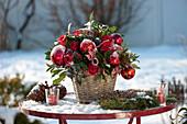 Weihnachtsstrauß mit roten Kugeln auf verschneitem Gartentisch