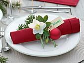 Rote Serviette weihnachtlich dekoriert mit Helleborus (Christrose)