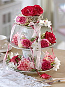 Aus Tellern und Tassen selbstgebaute Etagere mit Rosen und Nelken