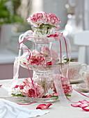Aus Glastellern und Gläsern selbstgebaute Etagere mit Dianthus 'Arthur'