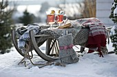 Sled with blanket, sweater, gloves, thermos