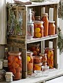 Eingemachte Tomaten, Peperoni, Essig und Kräuter in selbstgebautem Regal