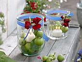 Einmachgläser als Windlichter mit Kerzen auf grünen Äpfeln (Malus)