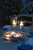 Windlichter mit Kerzen und Schale mit Hydrangea (Hortensienblüten)