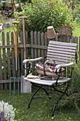 Korb mit Kleingeräten auf Gartenstuhl, Spaten und Grabgabel am Zaun