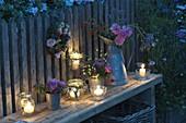 Abendliches Arrangement mit Windlichtern, Sträußen und Kranz aus Rosa