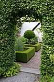 Torbogen aus Carpinus betulus (Hainbuche, Weißbuche), Blick in den Garten mit formalen Beeten und Prunus laurocerasus (Kirschlorbeer) Stämmchen Formschnitt