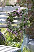 Kranz aus Gräsern und Trifolium pratense (Rotklee) an Stuhllehne