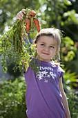 Mädchen mit frisch geernteten Möhren, Karotten (Daucus carota)