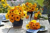Sträuße aus Calendula (Ringelblumen) in blauen Töpfen und als