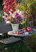 Herbstlicher Strauß auf Tisch im Garten
