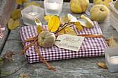 Geschenk in Serviette verpackt und dekoriert mit Quitte