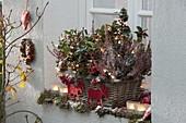 Vor-weihnachtlicher Korbkasten mit Lichterkette vor dem Fenster