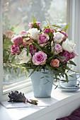 Strauß aus Rosa (Rosen), Eukalyptus und Farn in blauer Vase am Fenster