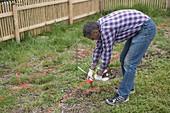 Gartenplanung : Mann zeichnet Gartenmitte mit rotem Farbpulver an