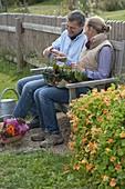 Mann und Frau auf Bank kosten selbstgeerntete Tomate (Lycopersicon)