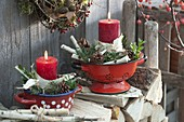Rote Kerzen mit Rinde und Zweigen von Betula (Birke), Zapfen von Pinus