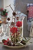 Glas mit Rosa 'Orange Sky' (Rosen), Zweige von Olea (Olive)