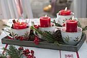 Schneller Adventskranz in weihnachtlichen Tassen mit roten Kerzen, Picea
