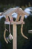 Kleines Vogelfutter-Haus mit Meise am Meisenknödel